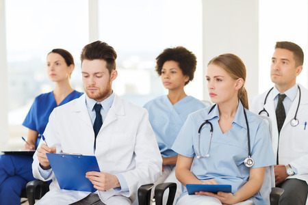 lecture hall: hospital, profession, people and medicine concept - group of happy doctors on seminar in lecture hall at hospital