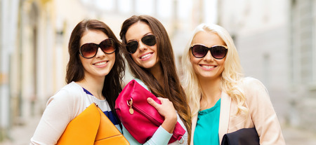 mujeres felices: holidays, tourism and happy people concept - three smiling women in sunglasses with bags in the city