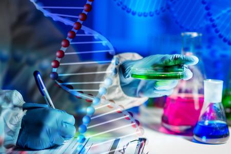 molecula: la ciencia, la química, la medicina y la gente concepto - cerca de joven científico con la muestra química tomando notas en el portapapeles y hacer pruebas o investigaciones en laboratorio sobre la estructura de molécula de ADN