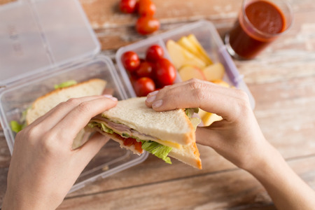 woman eating: healthy eating, storage, dieting and people concept - close up of woman hands with food in plastic container at home kitchen