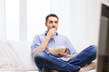 popcorn bowls: sports, food, happiness and people concept - young man watching tv and eating popcorn at home