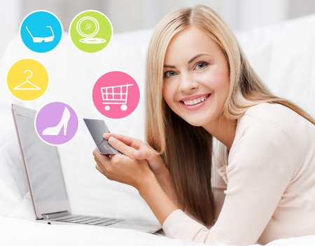orden de compra: compras en línea, la venta, la moda y la gente concepto - mujer feliz o ama de casa con el ordenador portátil y una tarjeta de crédito en casa Foto de archivo