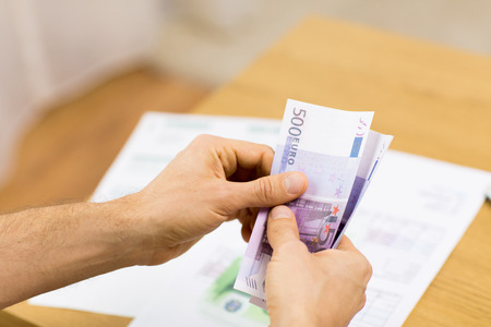 eur: savings, finances, economy and home concept - close up of man hands counting money at home Stock Photo