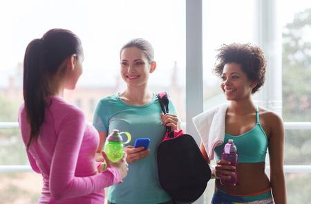 fitness, sport, opleiding en lifestyle concept - groep van gelukkige vrouwen met flessen water, smartphone en zak praten in de sportschool Stockfoto