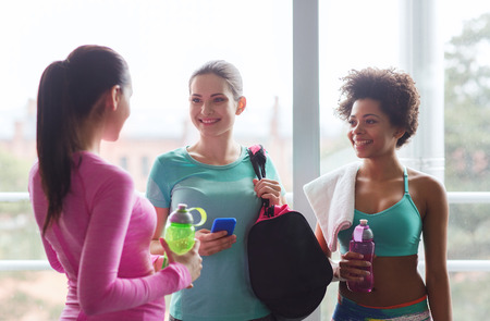 a workout: fitness, sport, training and lifestyle concept - group of happy women with bottles of water, smartphone and bag talking in gym