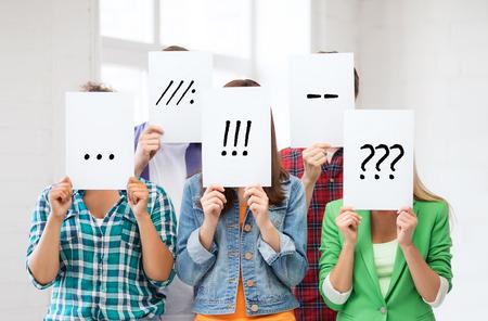 kommunikation: Menschen, Emotionen und Kommunikationskonzept - Gruppe von Freunden oder Studenten abdecken Gesichter mit Papierbögen