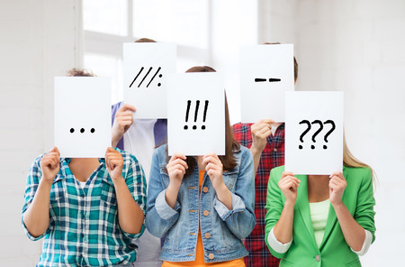 people, emotions and communication concept - group of friends or students covering faces with paper sheets. Stock Photo