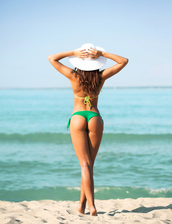 attractive ass: summer vacation, holidays and people concept - young woman sunbathing on beach Stock Photo