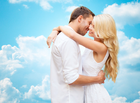 personas abrazadas: summer holidays, people, love and dating concept - happy couple hugging over blue sky and white clouds background