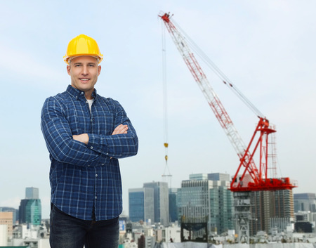 helmet construction: repair, construction, building, people and maintenance concept - smiling male builder or manual worker in helmet over city construction site background