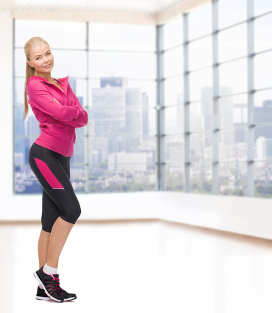 athletic wear: sport, fitness, people and weight loss concept - beautiful sporty young woman over gym background