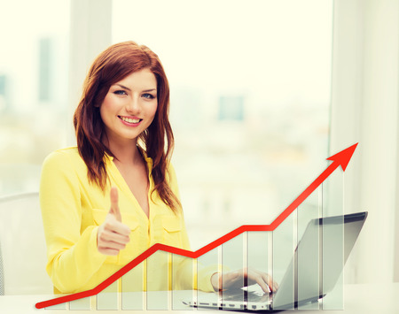 home business: people, technology, statistic sand business concept - smiling woman with laptop computer and growth chart showing thumbs up at home Stock Photo