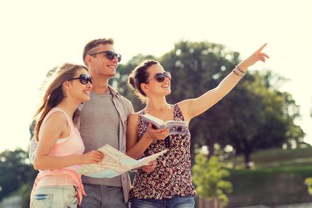 友情、旅行、観光、休暇、人々 の概念 - 地図と都市と笑みを浮かべて友達ガイド人差し指屋外