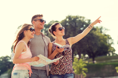 travel guide: friendship, travel, tourism, vacation and people concept - smiling friends with map and city guide pointing finger outdoors