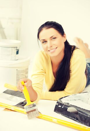 tenager: happy young woman with paintbrush and renovating tools