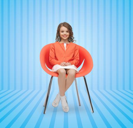 jolie petite fille: les gens, le bonheur, l'enfance et le concept de meubles - petite fille heureuse assis sur une chaise design bleu sur fond rayé