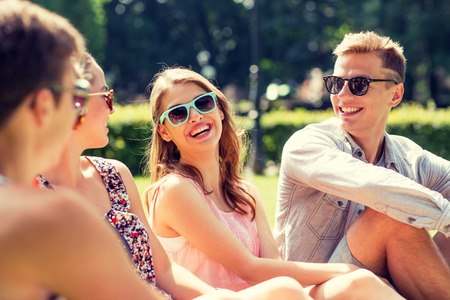 at leisure: friendship, leisure, summer and people concept - group of smiling friends outdoors sitting on grass in park