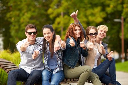 夏休み、教育、キャンパス、十代のコンセプト - 学生やティーンエイ ジャー親指を示すグループ