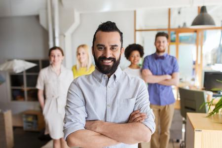 사업, 시작, 사람과 팀워크 개념 - 사무실에서 창조적 인 팀을 통해 수염을 가진 행복 한 젊은 남자