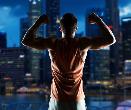 night shirt: sport, fitness, bodybuilding, strength and people concept - young man or bodybuilder showing biceps over night city background