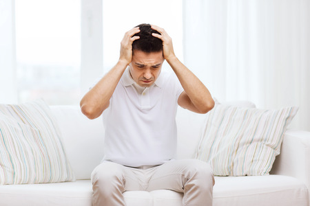 people, crisis, emotions and stress concept - unhappy man suffering from head ache at home Stock Photo