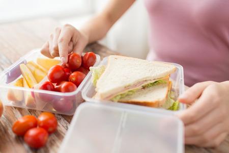 envases de plástico: la alimentación saludable, el almacenamiento, la dieta y el concepto de la gente - cerca de la mujer con la comida en un recipiente de plástico en la cocina en casa