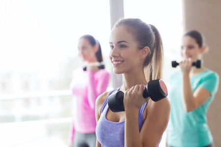 gym: fitness, sport, training and lifestyle concept - group of happy women with dumbbells flexing muscles in gym