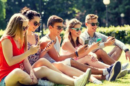 amistad: amistad, ocio, verano, la tecnología y la gente concepto - grupo de amigos sonrientes con los teléfonos inteligentes sentado en la hierba en el parque