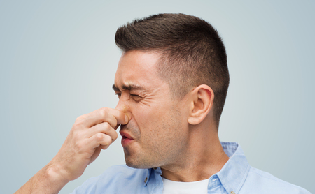 unpleasant: emotions, gesture and people concept - man wrying of unpleasant smell and closing his nose over gray background