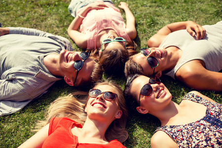 out in town: friendship, leisure, summer and people concept - group of smiling friends lying on grass in circle outdoors Stock Photo