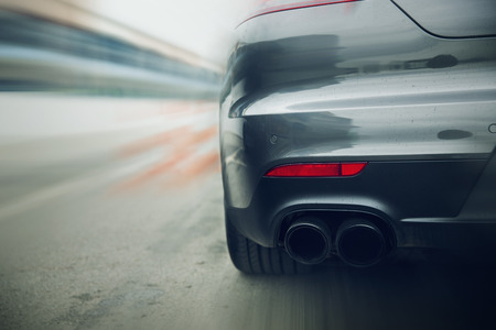 exhaust: transportation, speed, racing and road concept - close up of car riding on highway from back