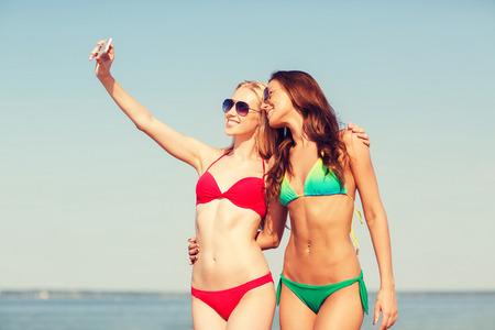 zomervakantie, vakantie, reizen, technologie en mensen concept - twee lachende jonge vrouwen op strand maken selfie met smartphone over blauwe hemelachtergrond Stockfoto