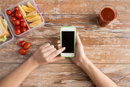 healthy eating, dieting, technology and people concept - close up of woman hands with blank smartphone and food in plastic container on table at home