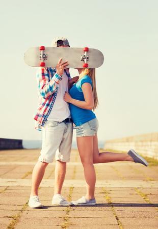 pareja de adolescentes: días de fiesta, vacaciones, el amor y el concepto de la gente - pareja besándose y ocultando sus rostros detrás del monopatín al aire libre