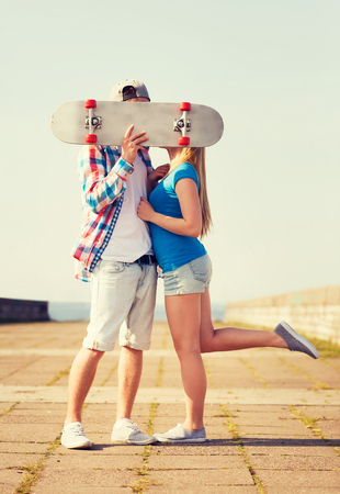 young couple hugging kissing: holidays, vacation, love and people concept - couple kissing and hiding their faces behind skateboard outdoors