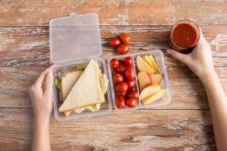lunch meal: healthy eating, storage, dieting and people concept - close up of woman hands with food in plastic container at home kitchen