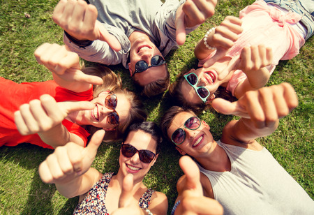 friendship, leisure, summer, gesture and people concept - group of smiling friends lying on grass in circle and showing thumbs up outdoors Stockfoto