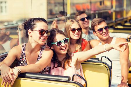 přátelství, cestování, prázdniny, léto a lidé koncept - skupina přátel úsměvem cestují autobusu