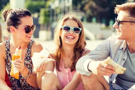 Freundschaft, Freizeit, Sommer und Menschen Konzept - Gruppe von Freunden lächelnd mit Sonnenbrille Sitzung mit der Nahrung auf Stadtplatz