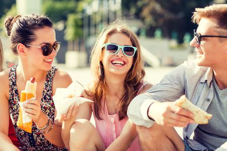 vriendschap, vrije tijd, zomer en mensen concept - groep van lachende vrienden in zonnebril zitten met voedsel op stadsplein