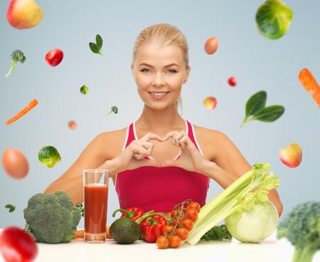 personas comiendo: personas, la alimentación saludable, el concepto vegetariano y cuidado de la salud - mujer feliz con la comida orgánica y la caída de las verduras que muestran el símbolo en forma de corazón sobre fondo gris
