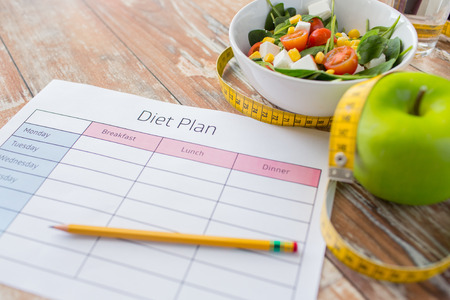 healthy life: healthy eating, dieting, slimming and weigh loss concept - close up of diet plan paper green apple, measuring tape and salad Stock Photo
