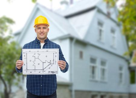 constructor: reparación, construcción, edificio, personas y concepto de mantenimiento - sonrientes constructor masculino o trabajador manual en casco con el modelo sobre vivir fondo casa
