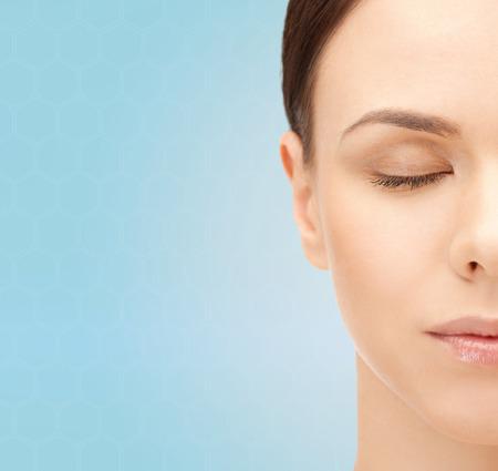 美しさ、人と健康コンセプト - 青い背景の上の美しい若い女性の顔