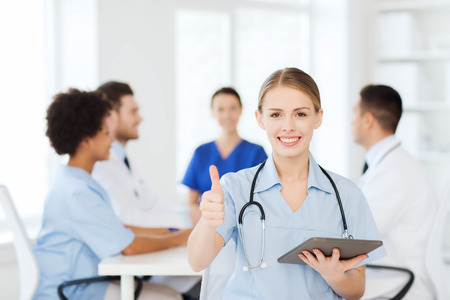 medics: clinic, profession, people and medicine concept - happy female doctor with tablet pc computer over group of medics meeting at hospital showing thumbs up gesture