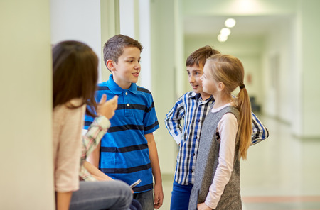 education, elementary school, children, break and people concept - group of smiling school kids talking in corridor Banco de Imagens