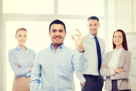 group of business people: office, business, and teamwork concept - friendly young smiling businessman with team on back showing ok-sign