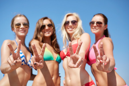 summer vacation, holidays, gesture, travel and people concept - group of smiling young women showing peace or victory sign over blue sky background