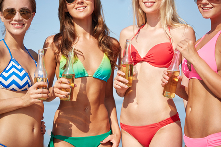 nonalcoholic beer: summer vacation, holidays, party, travel and people concept - close up of young women drinking lemonade on beach