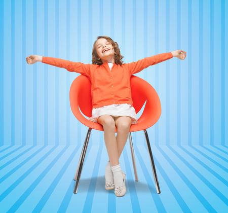 niños sentados: la gente, la felicidad, la infancia y concepto de mobiliario - niña feliz sentado en la silla con los brazos spreaded sobre fondo azul a rayas